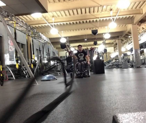 Wheelchair user battle ropes workout